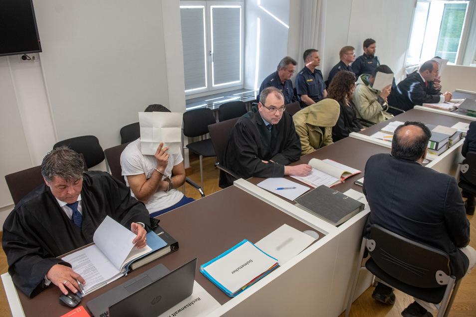 Die vier Angeklagten sitzen neben ihren Anwälten im Verhandlungssaal des Amberger Amtsgerichts.