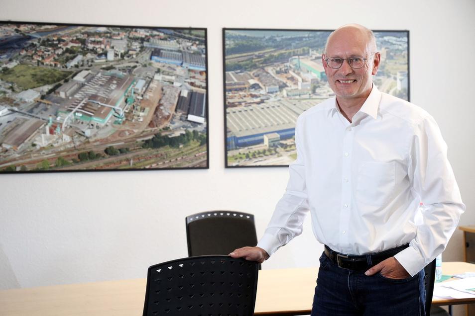 Uwe Reinecke ist Werksdirektor bei Feralpi Stahl in Riesa. In seinem Büro zeigen Luftbilder Ansichten des Stahlwerks.