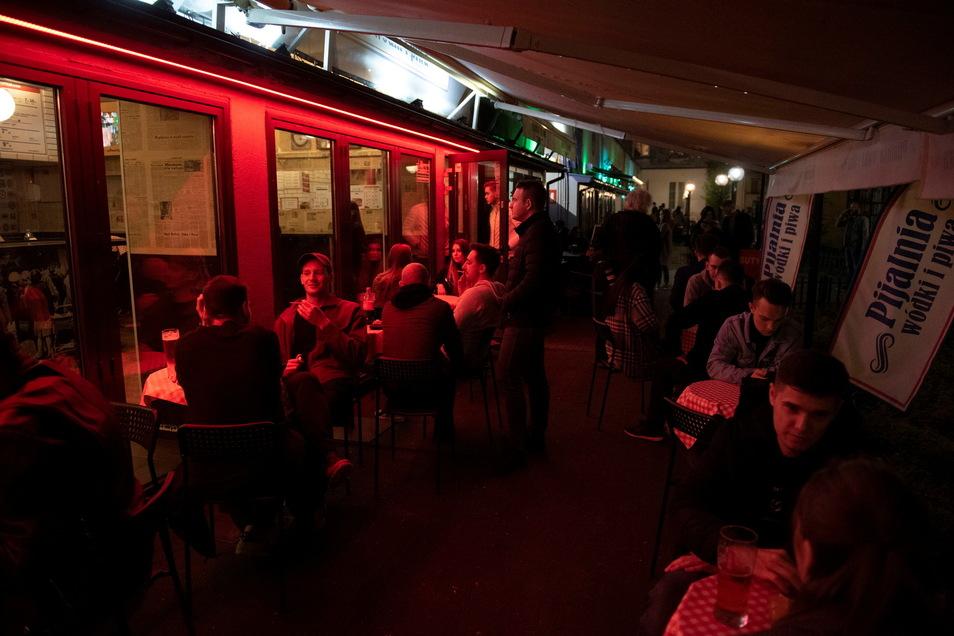 Menschen sitzen in Warschau vor einer Bar. Ab dem 15. Mai ist in Polen die Maskenpflicht im öffentlichen Raum aufgehoben.