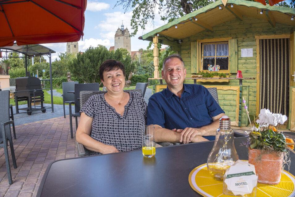 Anna und Marcel Koken haben es sich für einen Moment im neu gestalteten Garten ihres Strehlaer Ambiente Hotels gemütlich gemacht. Von dort gibt es einen Blick aufs Schloss – und zur anderen Seite hin zur Kirche.