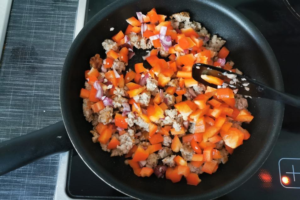 4. Schritt: Das Gemüse mit in die Pfanne geben und mit Paprika- sowie Knoblauchpulver würzen. Noch einige Minuten auf niedriger Temperatur anbraten.