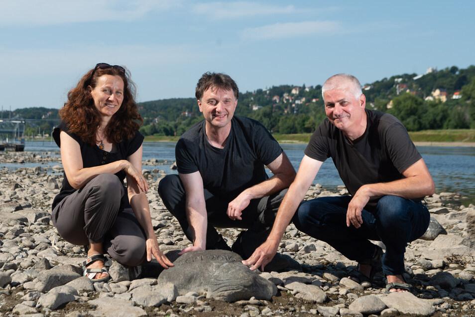 Anja Kaltofen, Elmar Vogel und Martin Kaden (v.l.) zeigen ihren Tolkewitzer Hungerstein. Bei niedrigem Pegel wie derzeit taucht er am Tolkewitzer Elbufer auf.