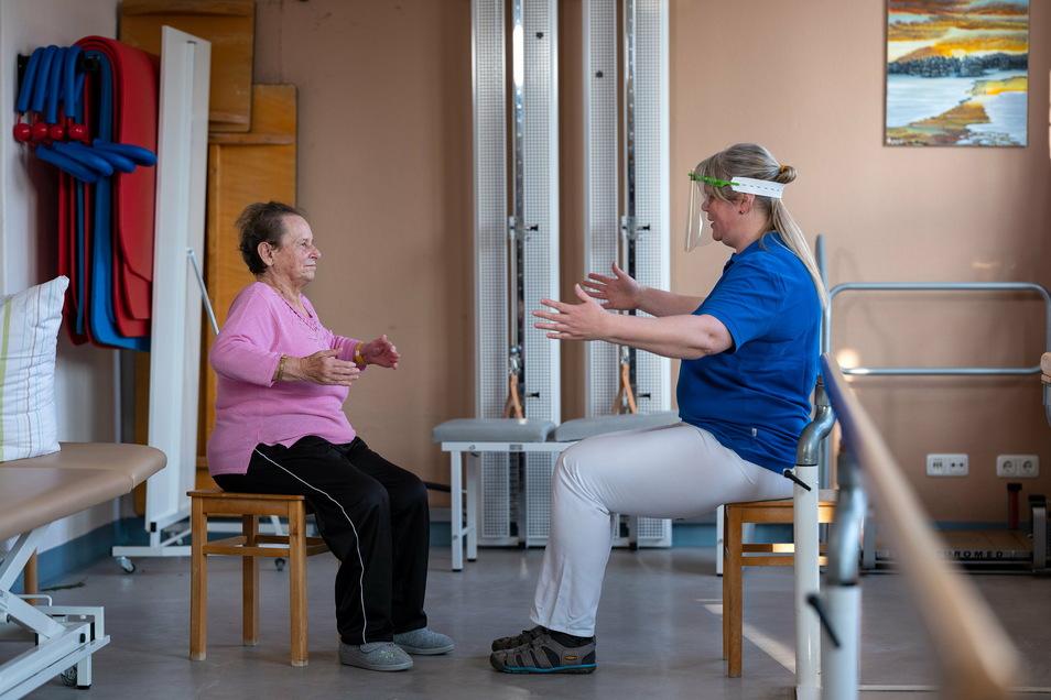 Physiotherapeutin Silvana Mohr von der Fachklinik für Geriatrie in Radeburg motiviert Gisela Druschke, ihren Brustkorb noch etwas mehr zu dehnen. Die 82-jährige Patientin hat eine Corona-Infektion