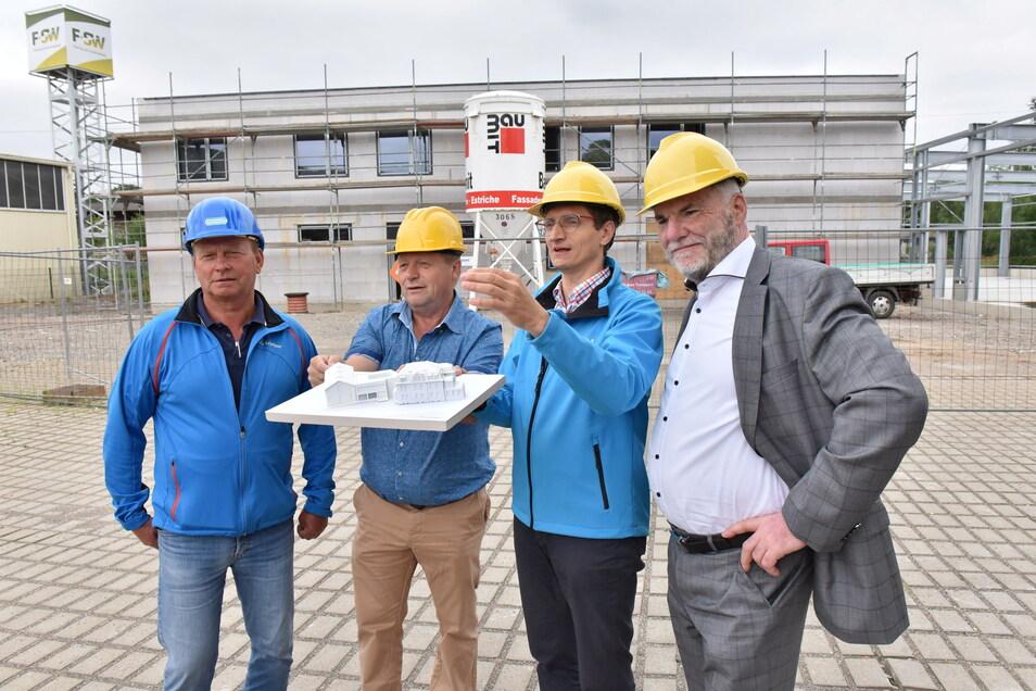 Oberbürgermeister Uwe Rumberg , SWF-Chef Matthias Leuschner, Matthias Koch vom Planungsbüro und Jens Weißhaupt vom Baubetrieb stehen vor dem Rohbau, der derzeit im hinteren Gelände entsteht.