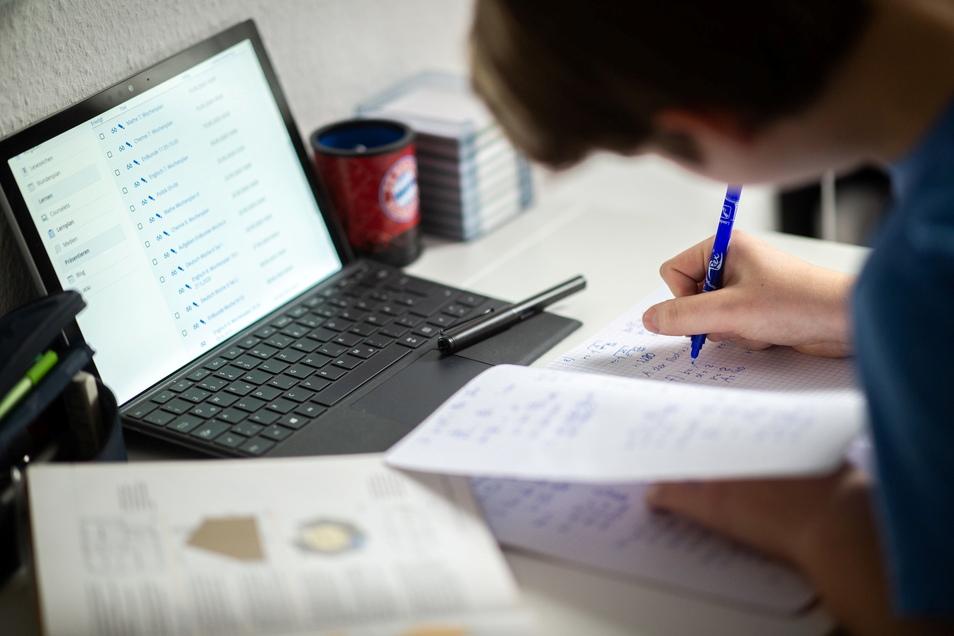 Ein Schüler sitzt in seinem Zimmer am Schreibtisch und erledigt Aufgaben im Rahmen des Homeschoolings.