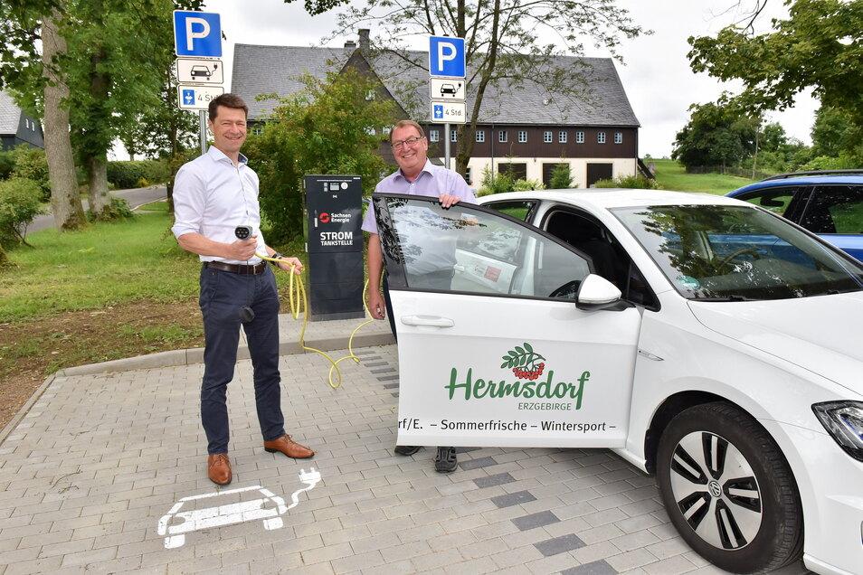 Gunnar Schneider von Sachsen Energie übergibt in Hermsdorf/E. die neue Ladesäule und einen Elektro-Golf an Bürgermeister Andreas Liebscher.