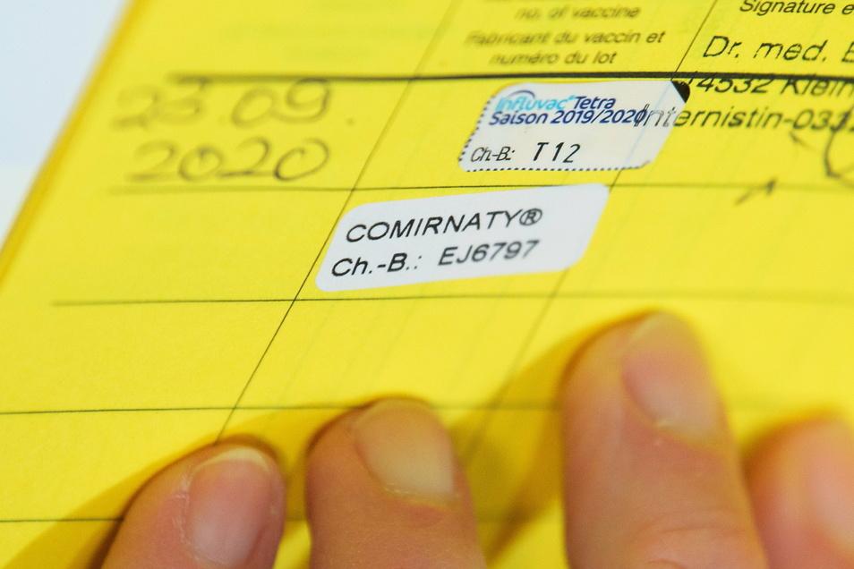 Eine Schwester hat im neu eröffneten Zentrum für das Impfen gegen Corona in Potsdam einen Aufkleber in den Impfausweis eines Patienten geklebt. Der Covid-19-Impfstoff von Biontech heißt Comirnaty.