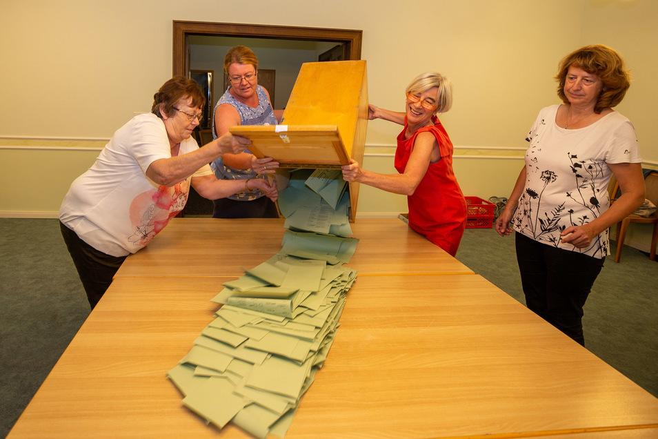 Frauen leeren in Kamenz die Wahlurne der Landtagswahl zur Auszählung.
