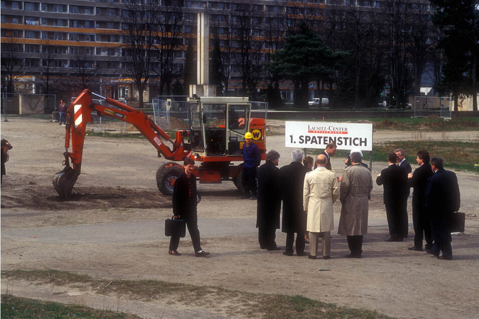 1994: Am 6. April erfolgte der erste Spatenstich – fast unbemerkt von der Öffentlichkeit. Am 31. März war die Bautafel gestellt worden, am 1. April offizieller Baubeginn.