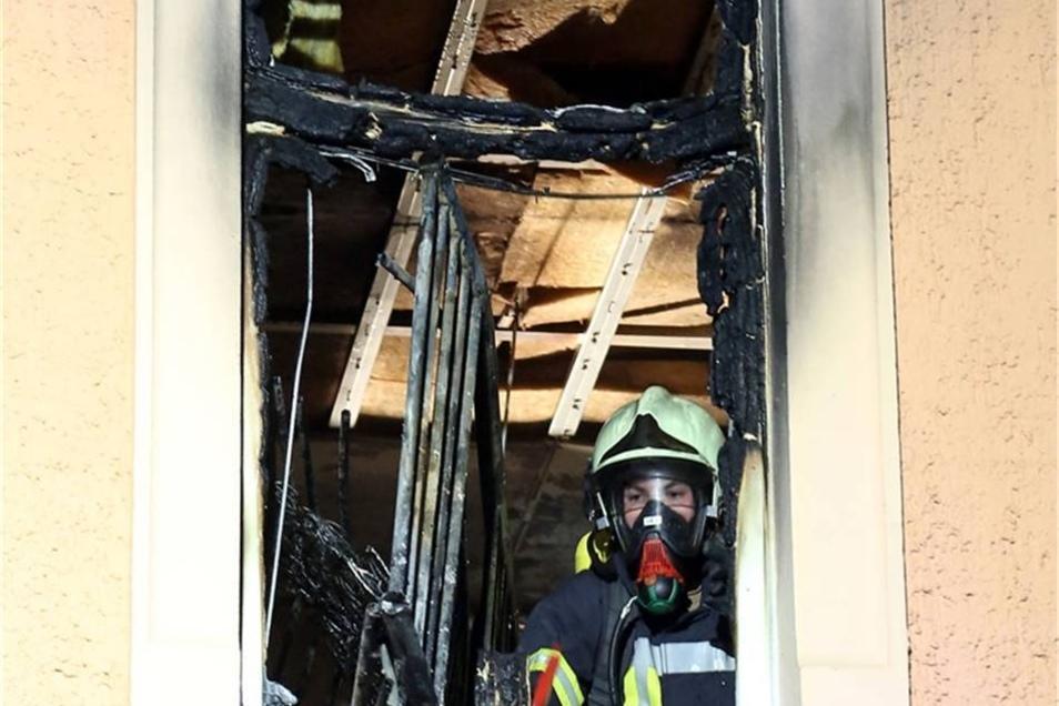 Ein Feuerwehrmann schaut aus dem ausgebrannten Zimmer.