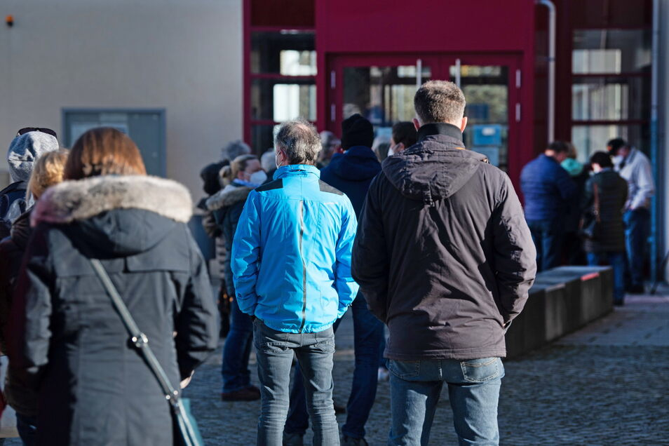 Bewohner der Region warten vor der Sporthalle des Berufsschulzentrums Radeberg auf den Massentest.