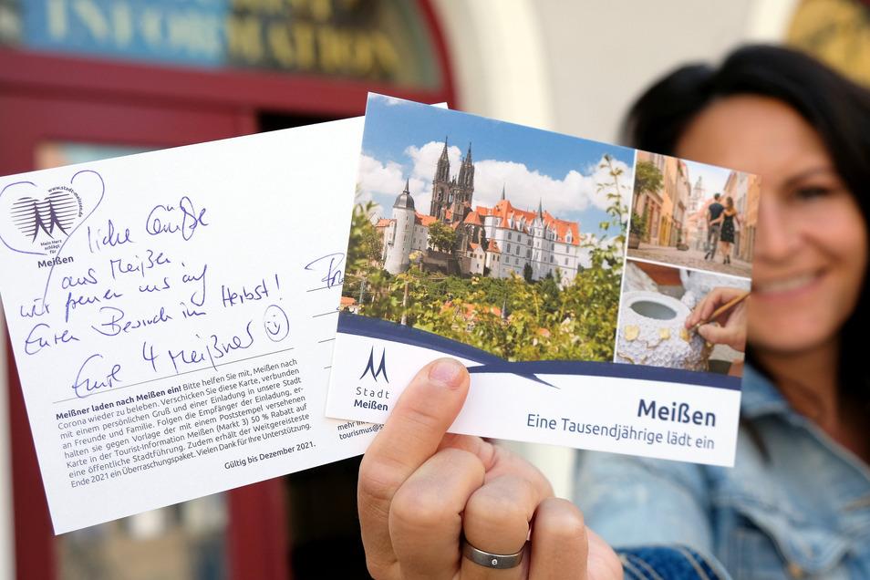 TIM-Chefin Christina Czach zeigt die Meißen-Postkarte, die in diesen Tagen an alle Haushalte in der Stadt verteilt wird.