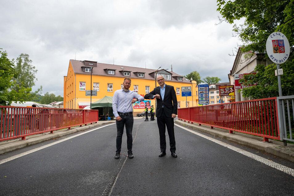 Der Bürgermeister von Dolni Poustevna Robert Holec (links) und Sebnitz Oberbürgermeister Mike Ruckh (rechts) treffen sich kurz vor 12 Uhr auf der Grenzbrücke zwischen Tschechien und Deutschland.