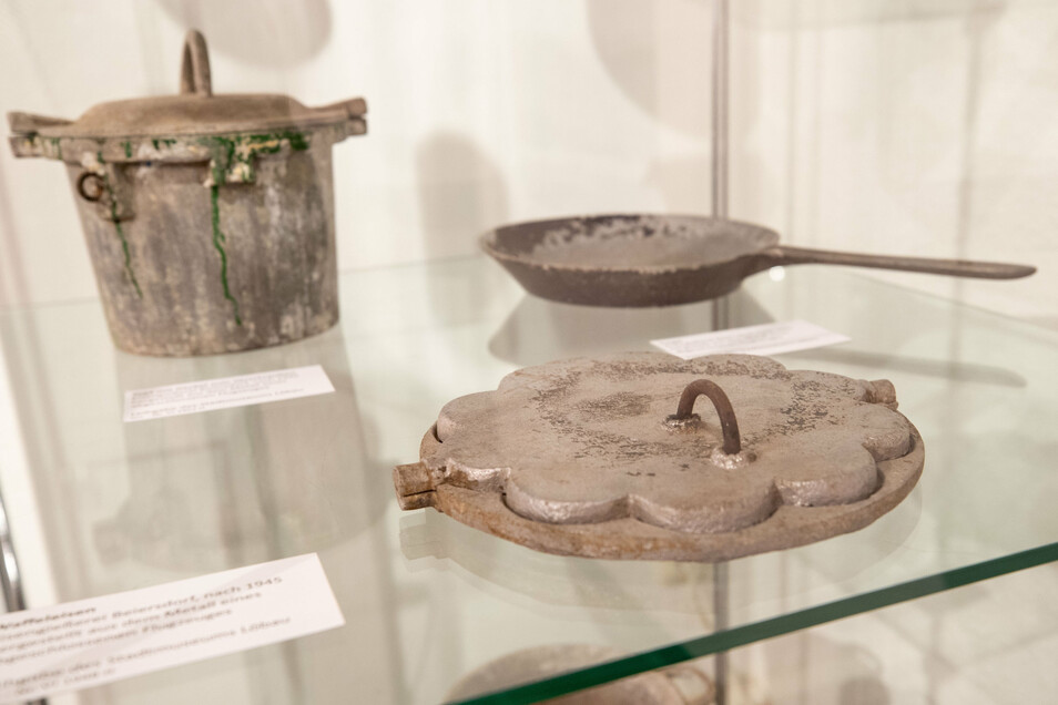 Ein Waffeleisen, ein Topf und eine Pfanne werden in einer Vitrine ausgestellt. Diese drei sind aus Resten von einem abgeschossenen Flugzeug geformt worden und kamen in der Küche zum Einsatz.