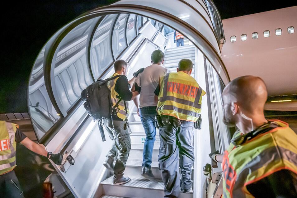 Polizeibeamte begleiten 2019 einen Afghanen nachts auf dem Flughafen Leipzig-Halle in ein Charterflugzeug.