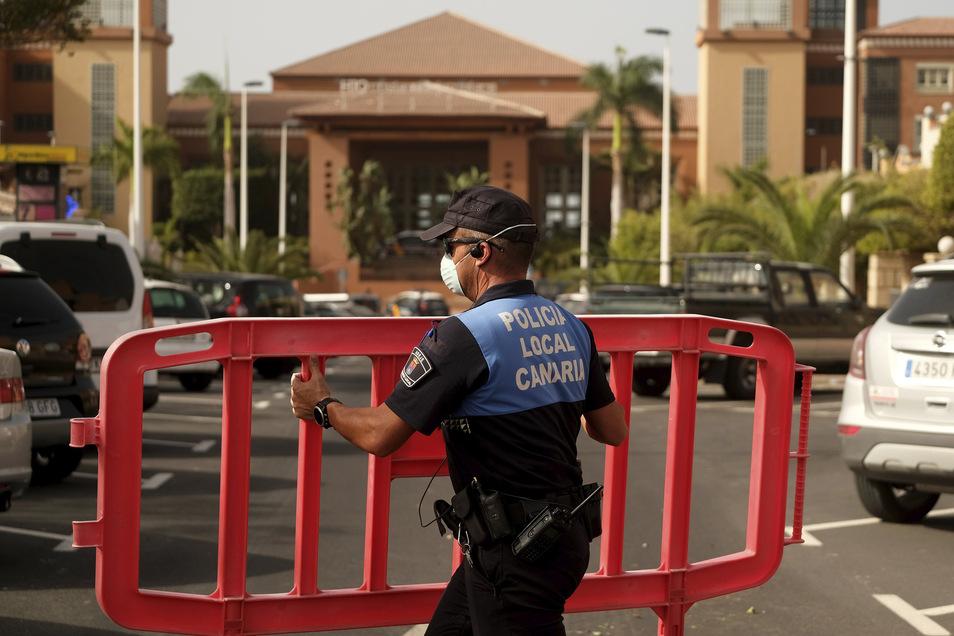 Ein Polizist setzt eine Sperre, die den Zugang zum Hotel H10 Costa Adeje Palace auf Teneriffa blockiert.