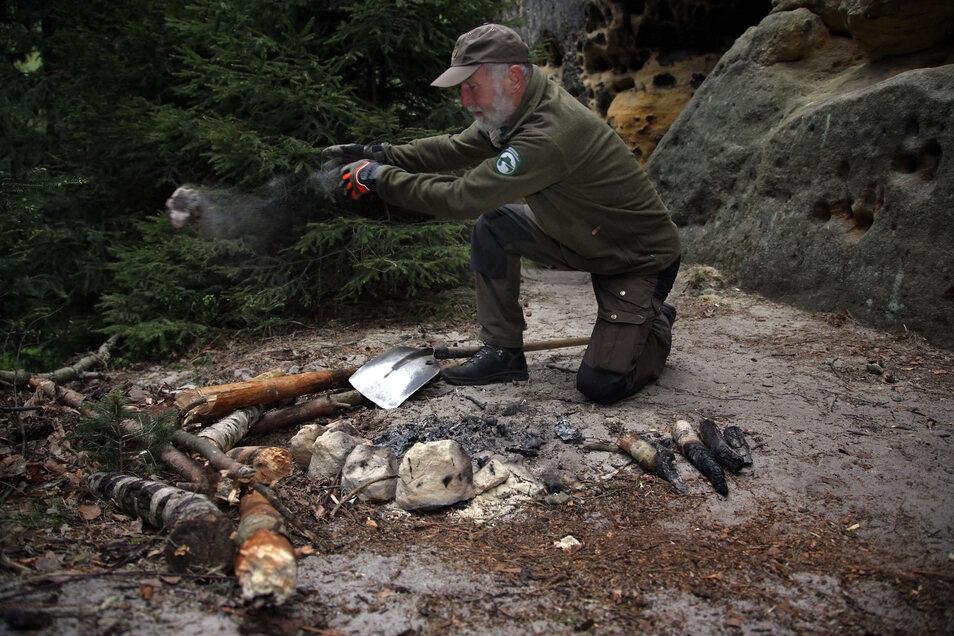 Nationalpark-Ranger Bernd Martin beseitigt die Feuerstelle im Rauschentor im Schmilkaer Gebiet.