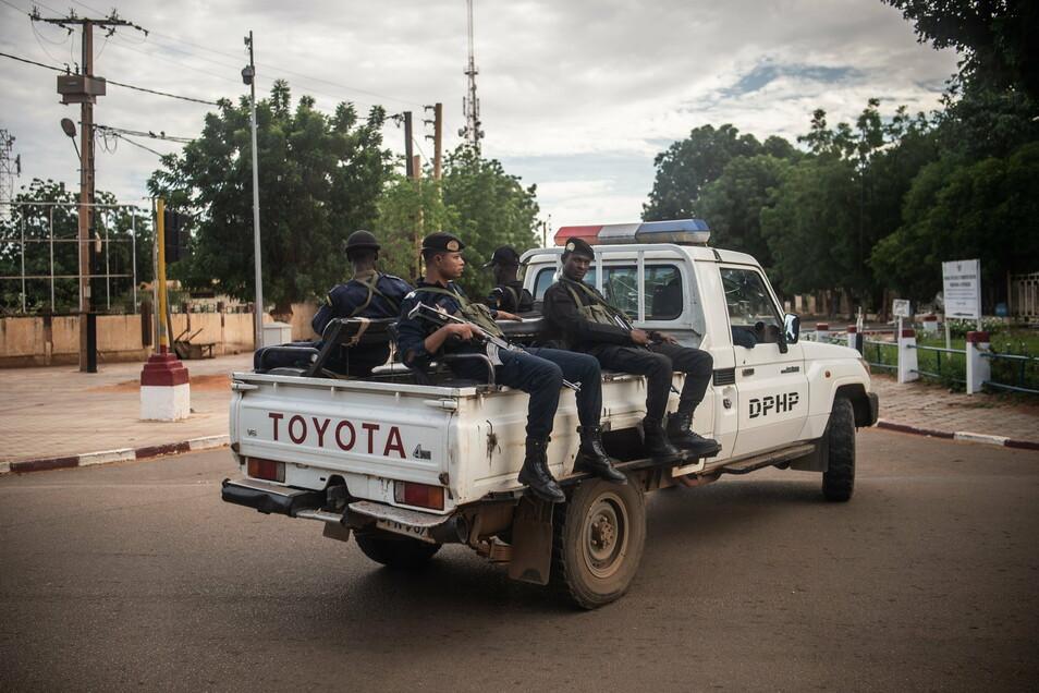 Bewaffnete Polizisten sitzen auf einem Toyota-Pickup in der Hauptstadt der Republik Niger. In Malis Nachbarstaat Niger haben Unbekannte ein Attentat verübt. Vermutlich wurden dabei mehr als 70 Menschen getötet.