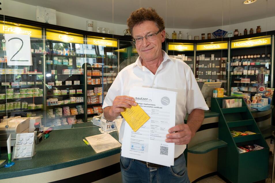 Thomas Köhler, Inhaber der Löwen Apotheke an der Badstraße in Radeberg, mit einem Impfpass und einem Impfnachweis. Ab Montag wollen er und seine Mitarbeiter den digitalen Impfpass ausstellen. Er hofft, dass bis dahin alle technischen Voraussetzunge