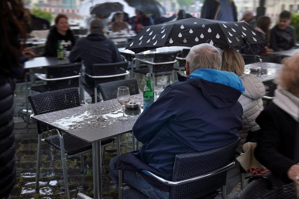 Auch ein Regenschauer kann die Gäste am Neumarkt nicht von ihren Plätzen vertreiben. Dann wird eben einfach der Regenschirm aufgespannt.
