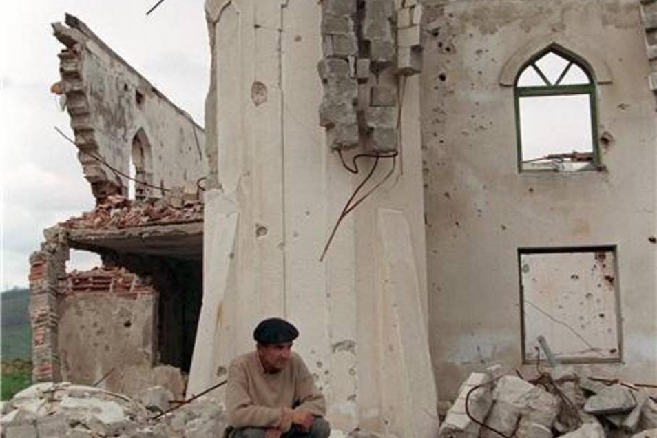 Traurig sitzt ein Moslem auf den Trümmern einer zerstörten Moschee im ehemals von serbischen Rebellen besetzten Sarajevo-Vorort Ilijas, aufgenommen am 2.5.1996.