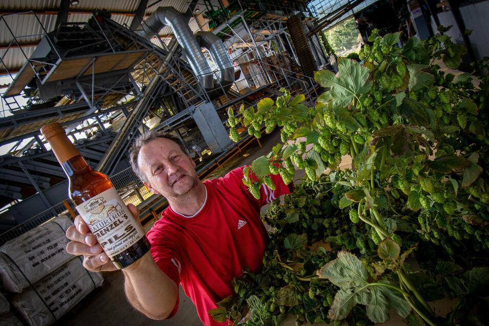 Reiner Joachim vor der Pflückmaschine. Der Geschäftsführer der Hopfen und Obst GmbH Schrebitz (Hoob), präsentiert eine Flasche Frenzel's Bräu aus Bautzen. Für dessen Herstellung liefert das Schrebitzer Unternehmen den Hopfen.