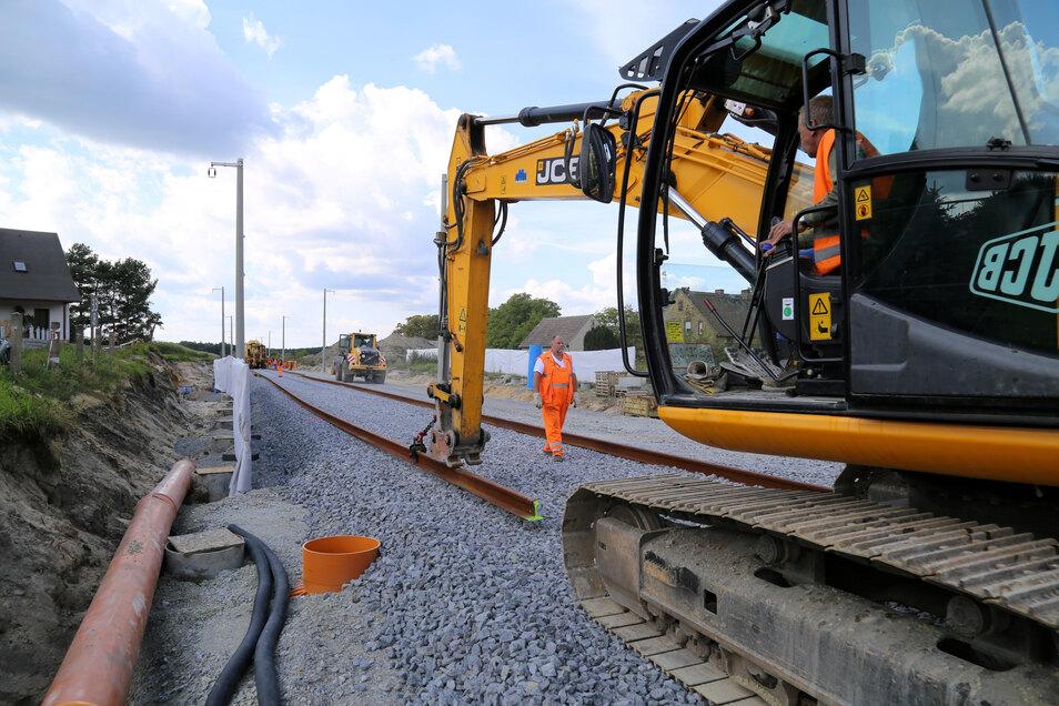 In Petershain wird schon seit langem gebaut. Hier schauen sich Neugierige an, wie der Gleisbauzug Schwellen verlegt und Gleisstränge verbindet.