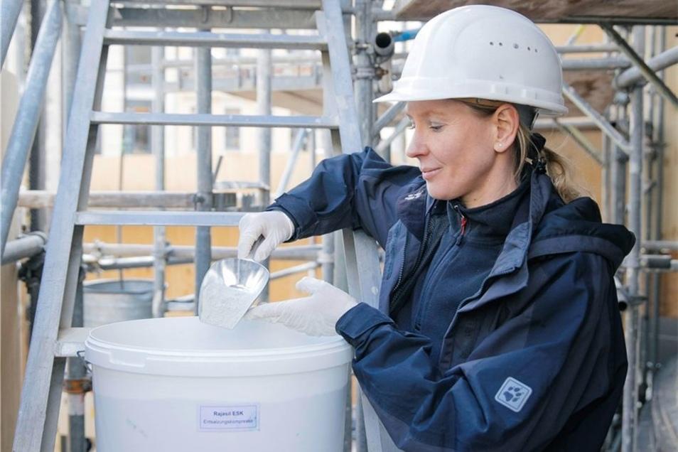 Nach der Reinigung wird Krause auf dem Gerüst Zellstoff mit Wasser und Tonmineralien für die Kompressenpaste anmischen.
