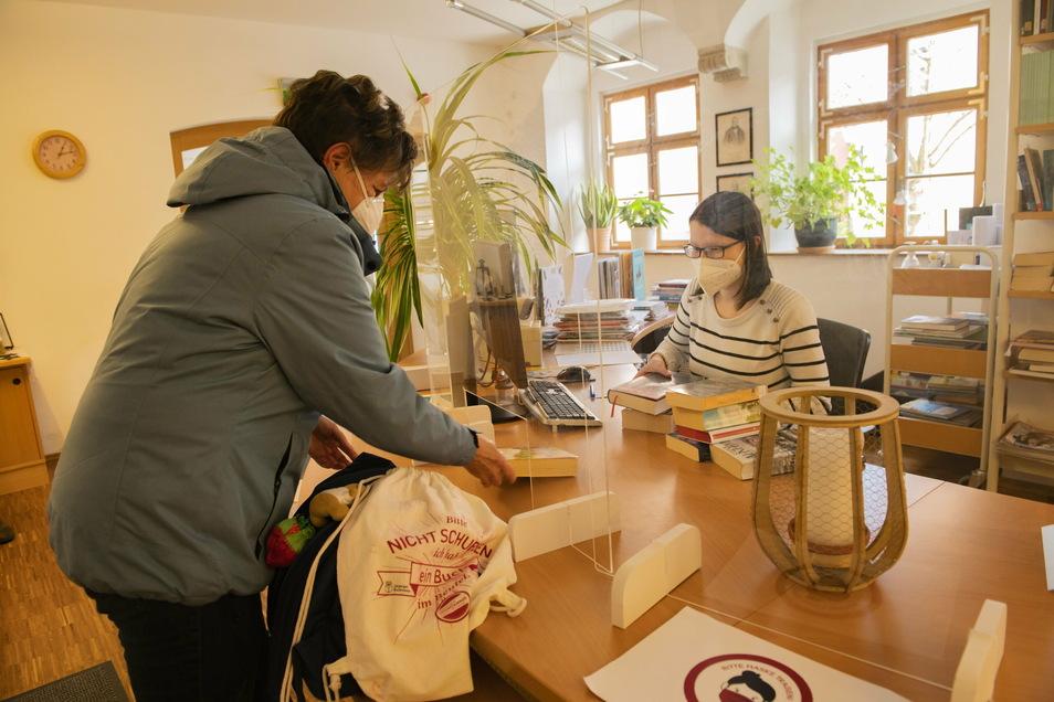 In der Karl-Preusker-Bücherei Großenhain nimmt Bibliotheksmitarbeiterin Melanie Richter ausgeliehene Bücher von Leserin Irene Hentschel zurück.