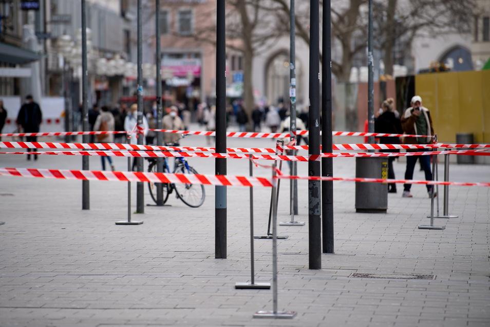 Passanten gehen durch die Fußgängerzone in München. Die Stadt hat die sogenannte Notbremse im Kampf gegen die Corona-Pandemie gezogen.