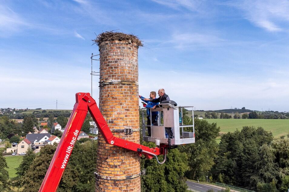 Zwei Mitarbeiter der Firma Kühn verfugen von einer Hubbühne aus den Schornstein neu.