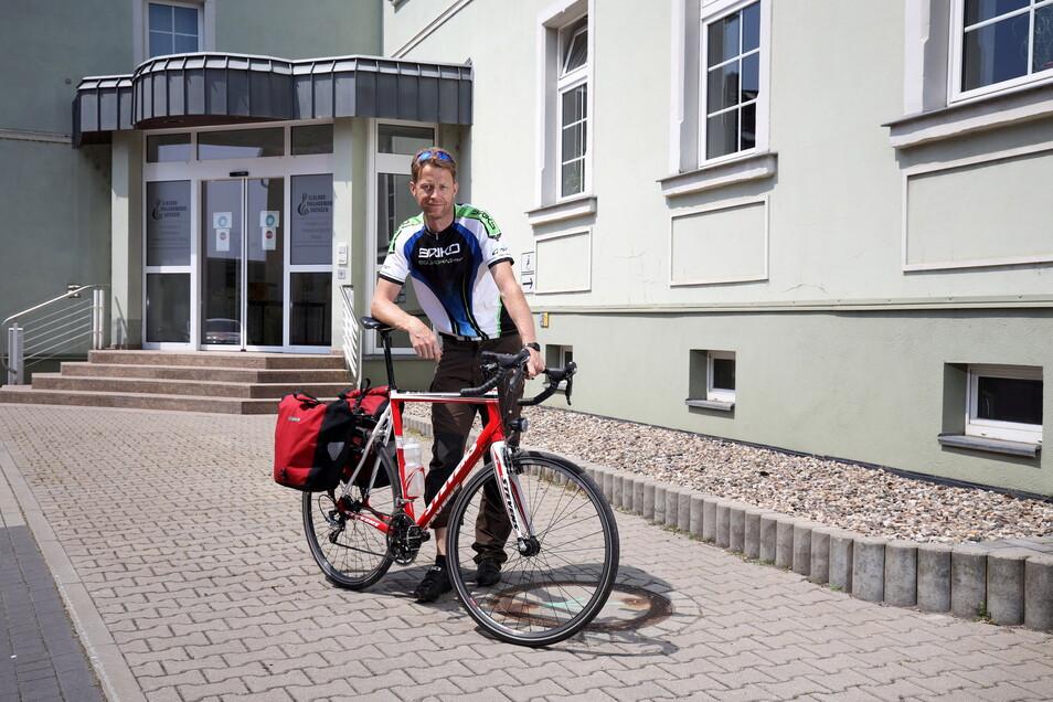 Andreas Dude mit seinem Rennrad vor dem Gebäude der Elbland Philharmonie Sachsen in Riesa. Mehrmals pro Woche radelt der Musiker aus Dresden hierher - unabhängig vom Wetter.