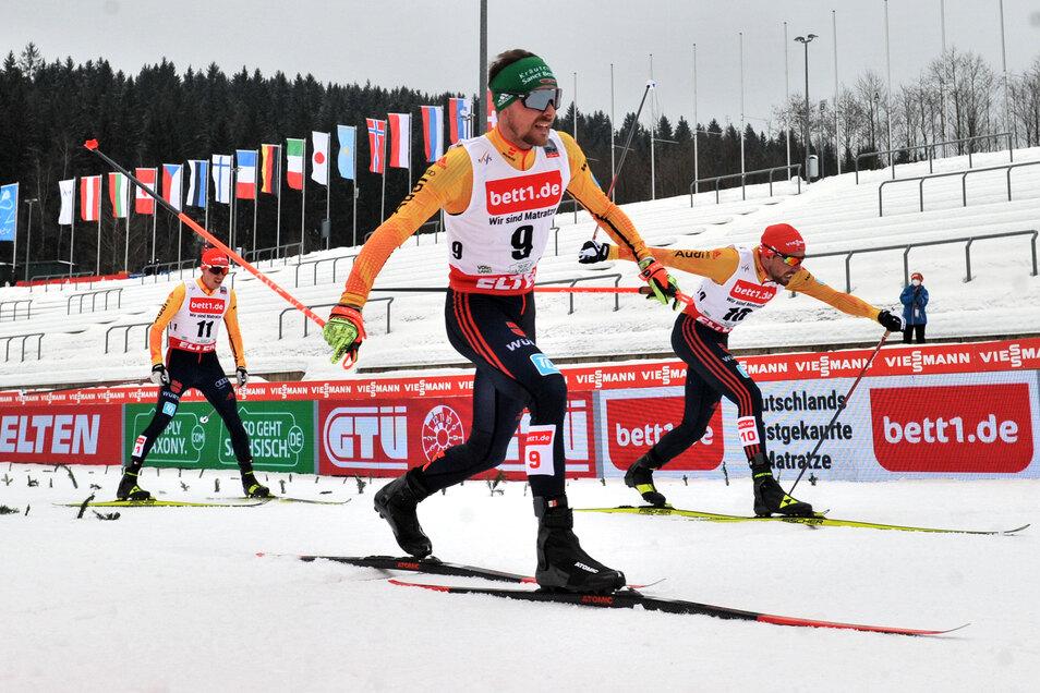 Eric Frenzel, Fabian Rießle und Johannes Rydzek laufen über die Ziellinie vor leeren Zuschauerrängen in der Vogtland-Arena von Klingenthal.
