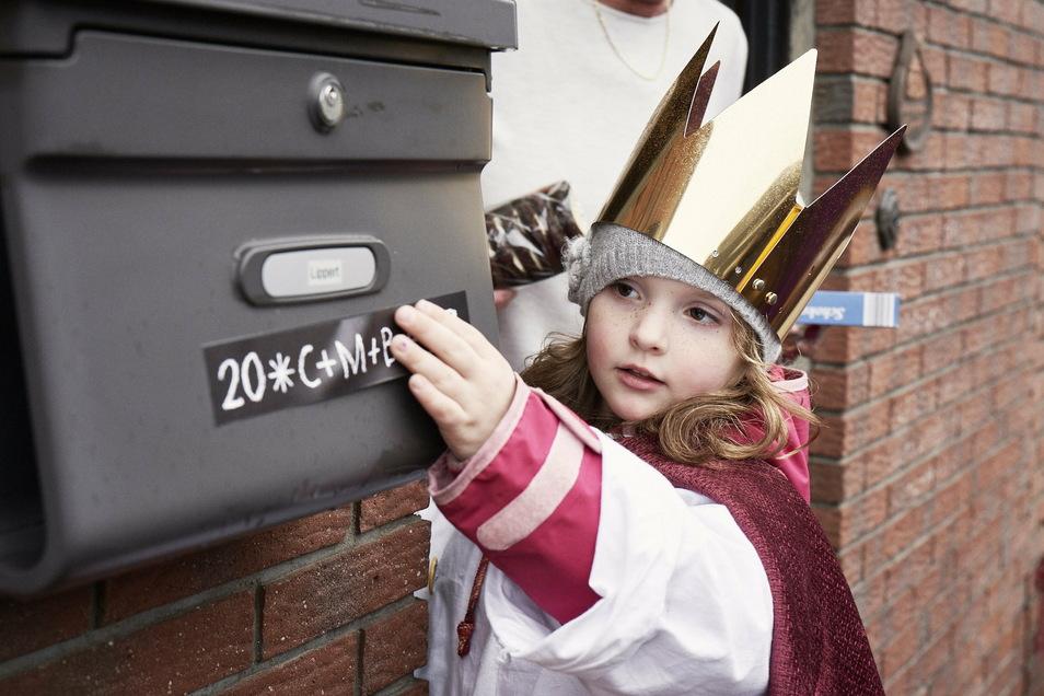Ein Bild aus schöneren Tagen: Eine kleine Sternsingerin bringt den Segensaufkleber selbst an einem Briefkasten an. Hoffentlich nächstes Jahr wieder.