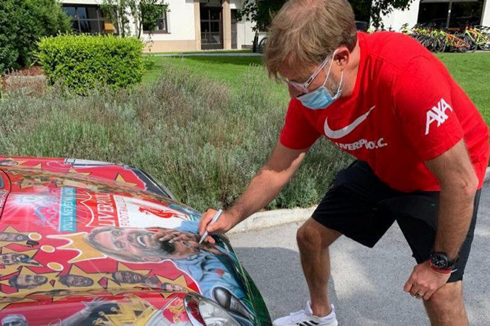 Der Beweis: Jürgen Klopp, coronagerecht mit Mund-Nasen-Schutz, unterzeichnet auf dem Wagen.