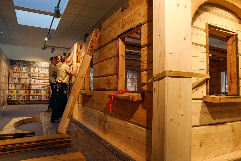 Die Mitarbeiter der Zimmerei Jens Vogt aus Waltersdorf bauen die Umgebindestube in die Bibliothek.