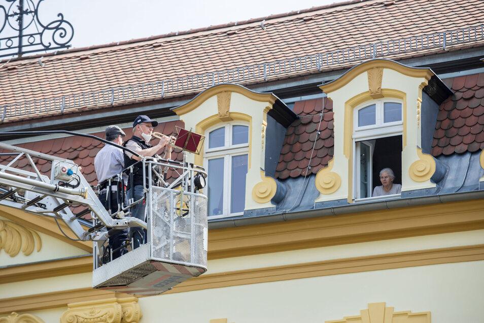 """Die Stadtfeuerwehr Niesky leistet Hilfe und fährt die beiden Blasmusiker mit der Drehleiter in die Höhe, damit diese am Altenpflegeheim """"Abendfrieden"""" ein Konzert spielen können für die Bewohner, die ihre Zimmer nicht verlassen dürfen."""