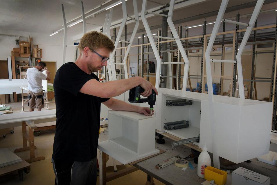 René Kaiser montiert in der Produktionshalle der Firma Rockhausen & Söhne ein Regal für eine Apotheken-Einrichtung.