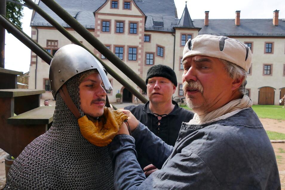 Sächsische.de-Redakteur Eric Mittmann (links) durfte sich auf der Burg Mildenstein als Ritter versuchen. Dazu bekam er von Burgvogt Helmut zu Schlorrendorf (rechts) und Kämpfer Matthias eine originalgetreue Rüstung angelegt.