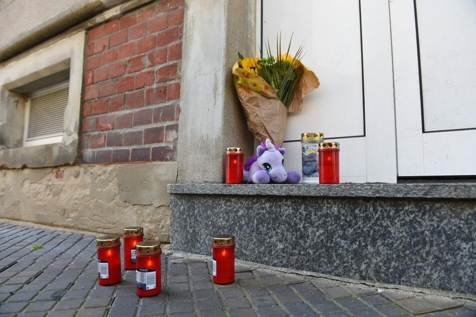 Vor dem Wohnhaus in Hartha stehen Kerzen und Blumen sowie ein Kuscheltier.