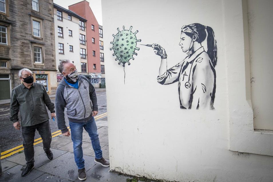Großbritannien, Edinburgh: Passanten gehen an dem öffentlichen Kunstwerk von «The Rebel Bear» vorüber, das eine Ärztin zeigt, die Impfstoff in ein Coronavirus injiziert.