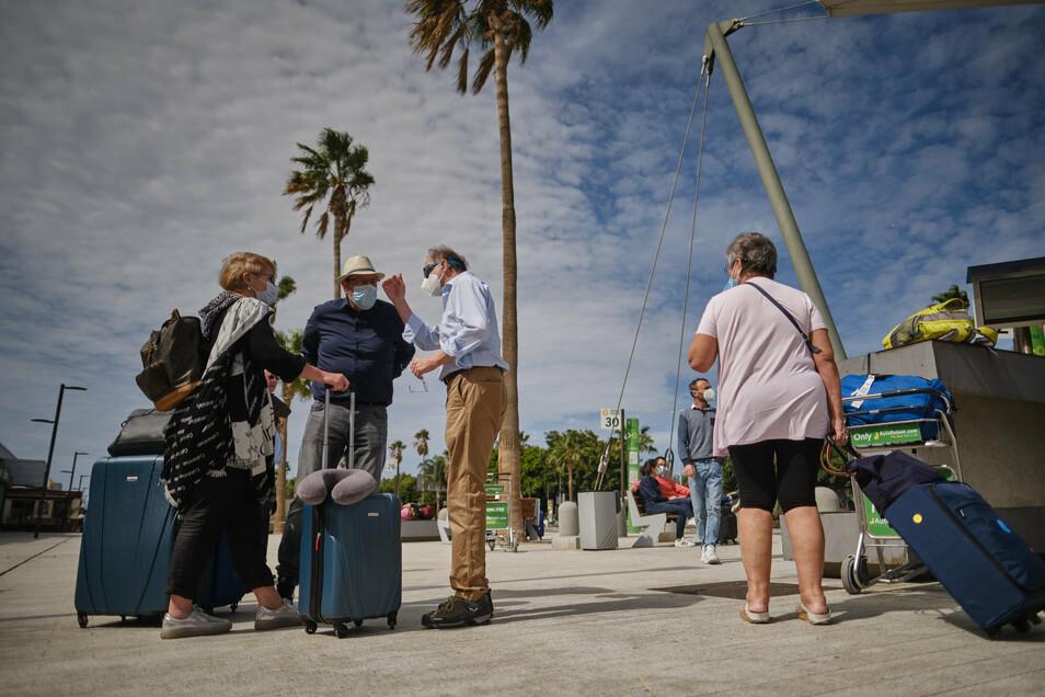 Eine Touristen-Gruppe wartet vor dem Flughafen Teneriffa Süd auf einen Bus. Deutsche und britische Touristen trafen an diesem Wochenende erstmals wieder auf Teneriffa ein.