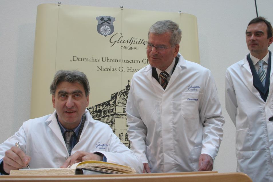 Der Chef der Swatch Group, Nick Hayek trug sich nach der Stiftungsunterzeichnung ins Goldene Buch der Stadt ein. Altbürgermeister Frank Reichel und der damalige GO-Geschäftsführer Dr. Frank Müller schauen zu.