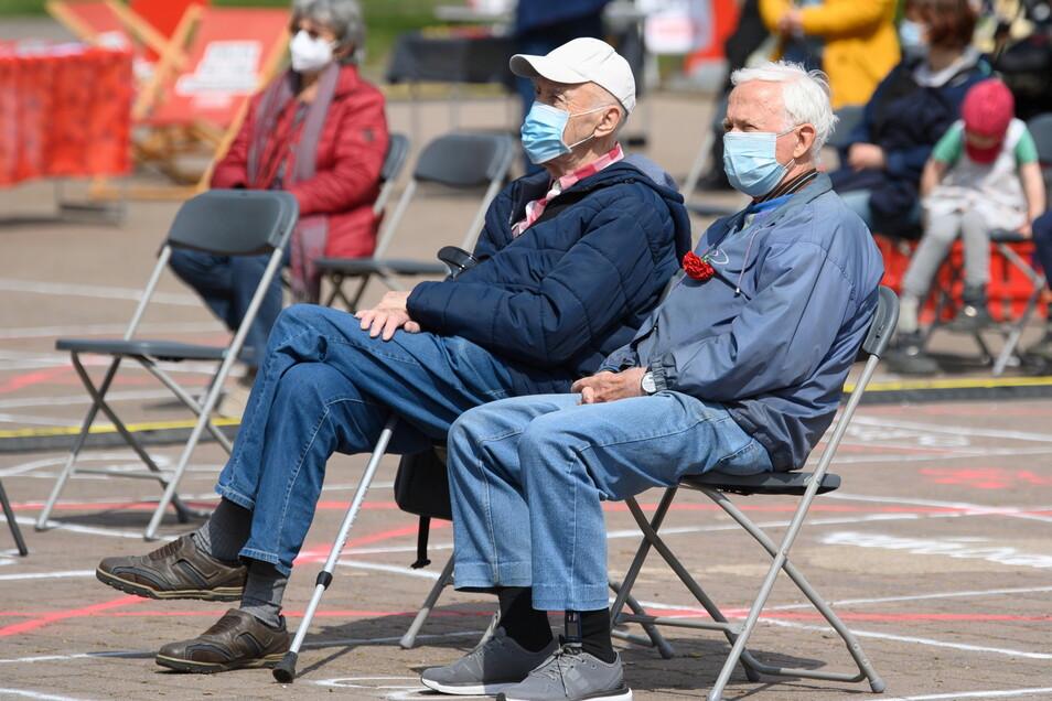 Zwei Rentner sitzen bei einer Veranstaltung der Partei Die Linke zum 1.Mai Feiertag vor einer Bühne im Alaunpark in der Dresdner Neustadt.