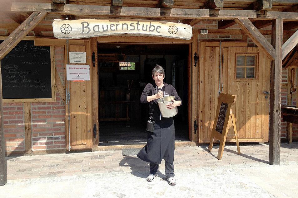 """Anke Stephan gehört zu den """"Bauernstubenmädels"""" an der Krabatmühle Schwarzkollm. Hier rührt sie eine Portion Plinsenteig an – nur fürs Foto vor der Tür. Ansonsten wird das in der Küche erledigt."""