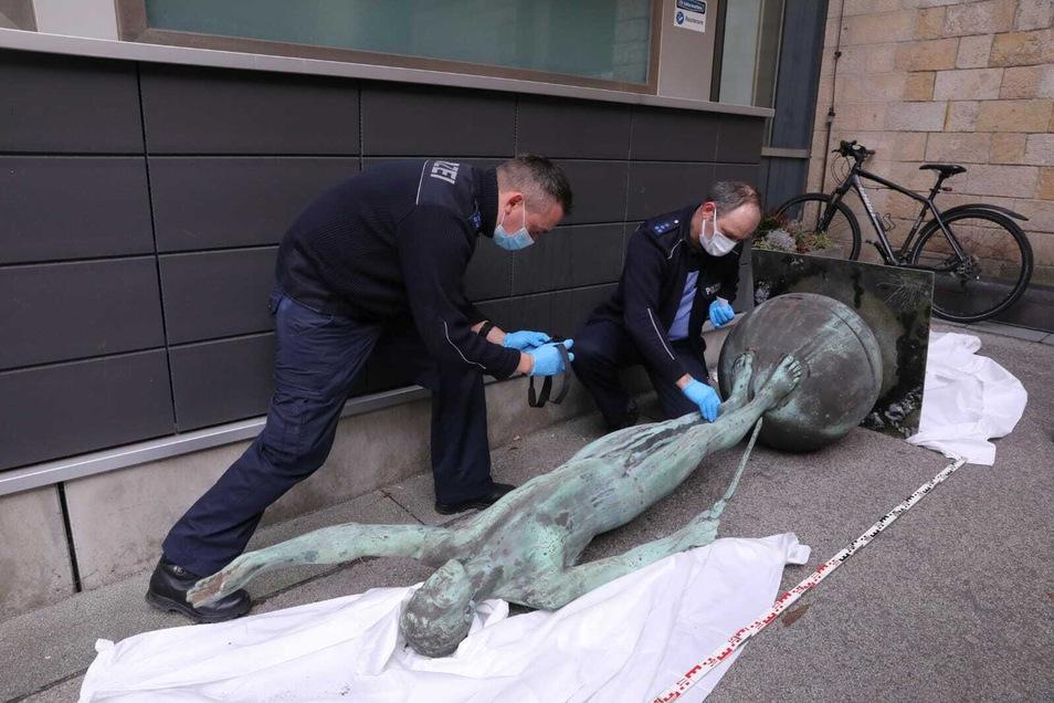 Polizeibeamten suchen Spuren der Täter an der gestohlenen Statue vom Urnenhain Tolkewitz.