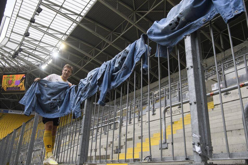 Marco Hartmann hängt vor dem Spiel gegen Osnabrück die Minge-Jeansjacken an den Zaun des K-Blocks. Einige Exemplare sollen für einen guten Zweck versteigert werden.