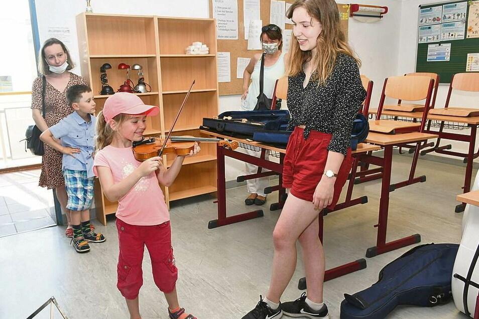Mit Eifer versucht sich die sechsjährige Marie auf der Geige und möchte das Instrument am liebsten gar nicht mehr aus der Hand geben. Musikschülerin Lena Krahl hat für die Kleine ein paar Tipps parat.