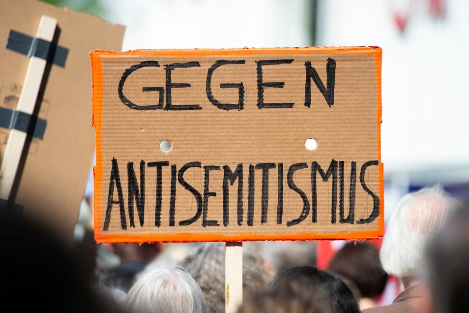 """Ein Person hält bei einer Kundgebung eines Bündnisses gegen Antisemitismus ein Plakat mit der Aufschrift """"Gegen Antisemitismus"""" in die Höhe."""