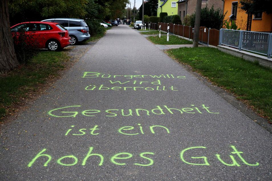 Mit Sprüchen auf der Fahrbahn der Sackgasse protestieren Zeithainer gegen das Bauprojekt in ihrer unmittelbaren Nachbarschaft an der Langenberger Straße.